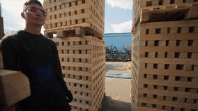 A young worker in uniform walks between wooden pallets in distribution outdoor warehouse. Slow motion. Wide view stock footage