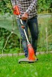Young worker using a lawn trimmer mower cutting grass in a blurred nature background.  Stock Image