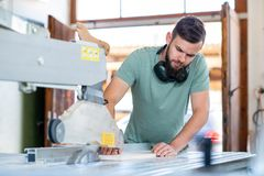 Young worker in a carpenters workshop using saw. Young worker using saw in a carpenters workshop royalty free stock photo