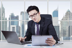Young worker using tablet and laptop Stock Photo