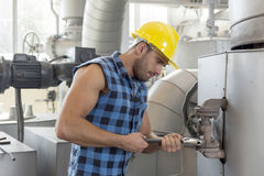 Young worker using wrench on industrial machine Royalty Free Stock Photo