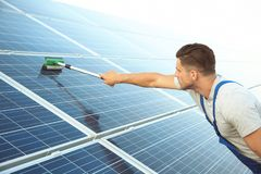 Young worker washing solar panels after installation Stock Images