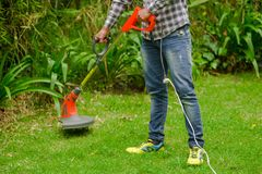 Young worker wearing jeans and long sleeve shirt and using a lawn trimmer mower cutting grass in a blurred nature. Background Royalty Free Stock Photo