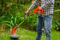 Young worker wearing jeans and long sleeve shirt and using a lawn trimmer mower cutting grass in a blurred nature. Background Stock Photography