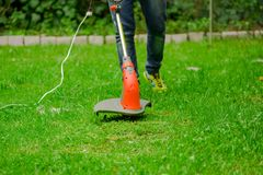 Young worker wearing jeans and using a lawn trimmer mower cutting grass in a blurred nature background.  Royalty Free Stock Photography