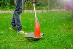 Young worker wearing jeans and using a lawn trimmer mower cutting grass in a blurred nature background.  Royalty Free Stock Photo