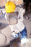 Young worker while welding metal. In a steel mill Stock Photos