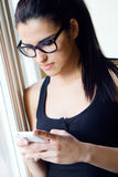 Young worker woman with smartphone in her office Stock Photos