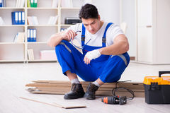 The young worker working on floor laminate tiles Royalty Free Stock Image