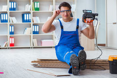 The young worker working on floor laminate tiles. Young worker working on floor laminate tiles royalty free stock images