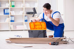 The young worker working on floor laminate tiles. Young worker working on floor laminate tiles royalty free stock photos