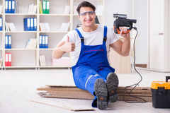 The young worker working on floor laminate tiles. Young worker working on floor laminate tiles stock images