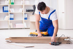 The young worker working on floor laminate tiles. Young worker working on floor laminate tiles stock image