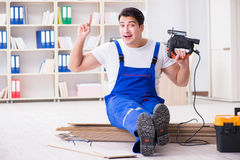 The young worker working on floor laminate tiles. Young worker working on floor laminate tiles stock photo