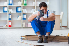 The young worker working on floor laminate tiles. Young worker working on floor laminate tiles royalty free stock image