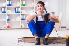 The young worker working on floor laminate tiles. Young worker working on floor laminate tiles royalty free stock photography