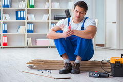 The young worker working on floor laminate tiles Stock Images