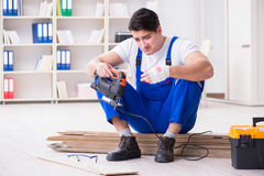 The young worker working on floor laminate tiles. Young worker working on floor laminate tiles Royalty Free Stock Photo