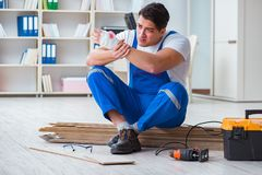 The young worker working on floor laminate tiles. Young worker working on floor laminate tiles Stock Photography
