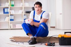 The young worker working on floor laminate tiles. Young worker working on floor laminate tiles Stock Photos