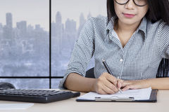 Young worker writes on paperwork Stock Image