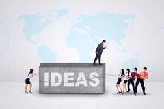 Young workers with ideas. Group of young entrepreneurs try to move a stone with a text of ideas Royalty Free Stock Photo