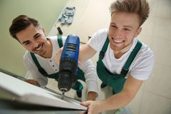 Young workers installing drywall, above view. Home repair service. Young workers installing drywall indoors, above view. Home repair service stock photography
