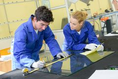 Young workers measuring pane glass. Young workers measuring pane of glass Stock Photography