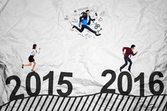 Young workers racing to get success. Three young businesspeople racing to get success by jumping and running above numbers 2015 to 2016 Royalty Free Stock Photo