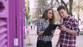 Young workers on the street: writing on a notebook and using phone stock video