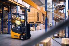 Young warehouse workers working together. Young workers working together. Woman forklift driver and a men in a warehouse royalty free stock photos