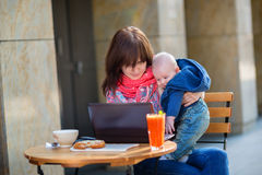 Young working mother with her son in a cafe. Young working mother with her little son in a cafe Stock Images