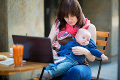 Young working mother with her son in a cafe royalty free stock photo