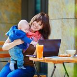 Young working mother with her son in a cafe. Young working mother with her little son in a cafe Royalty Free Stock Images