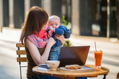Young working mother with little son in a cafe stock photo