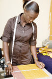Young working woman. This young seamstress checks the measurements of its pieces of fabric Stock Image