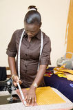 Young working woman. This seamstress metrs pieces of fabric before sewing them because it must respect the measures taken on its customers Royalty Free Stock Photography