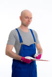 Young workman in blue dungarees with clipboard. In front of white background Royalty Free Stock Photography