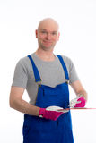 Young workman in blue dungarees with clipboard. In front of white background Royalty Free Stock Photo