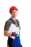 Young workman in blue dungarees with clipboard. In front of white background Royalty Free Stock Photos