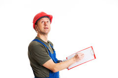 Young workman in blue dungarees with clipboard Stock Image