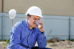 Young workman sipping coffee on a building site Stock Photos