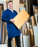 Young workman standing with plywood pieces Stock Photos