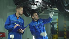 Young workshop employees working together underneath a lifted car stock video footage