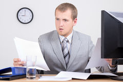 Young worried accountant doing paperwork in office Royalty Free Stock Photos