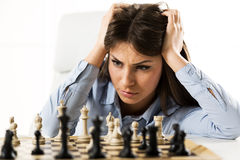 Young Worried Businesswoman In Front Of The Chessboard Stock Photography