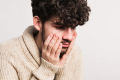 Portrait of a young man in woollen cardigan in a studio. A young worried handsome man in beige woollen cardigan in a studio. Copy space Royalty Free Stock Photo