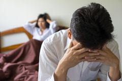 Young worried man on bed. Unhappy couple having problem in bedroom. stock photo