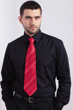 Young worried man in black shirt and red necktie Royalty Free Stock Image
