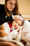 Young worried mother checking sick daughters temperature Stock Images